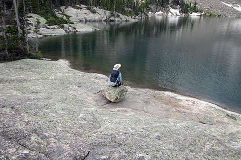 Hiker sitting on lone boulder overlooking lake
