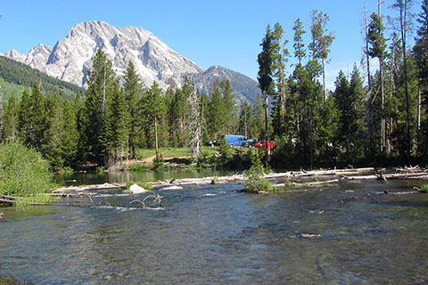 Vehicles parked seen at the String Lake Trailhead with Mount Moran in the background