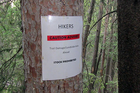 Hikers Caution Advised trail sign warning of damage from a landslide