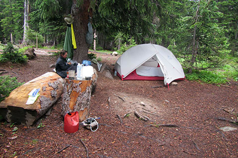 Hiker at campsite with tent and cooking gear