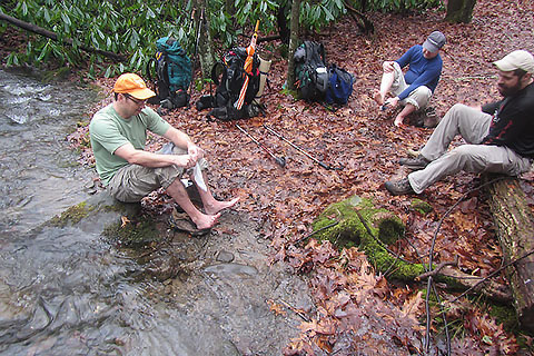 Backpackers drying their feet and putting on their socks and shoes.